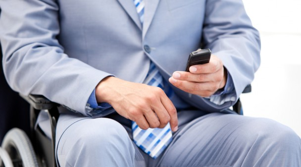 Close-up of a businessman sitting on a wheelchair sending a text