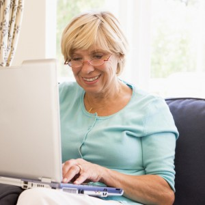 Woman in living room with laptop smiling