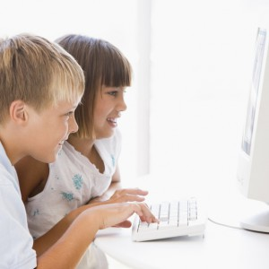 Two young children in home office with computer smiling