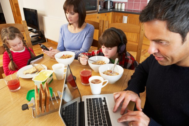 Family Using Gadgets Whilst Eating Breakfast Together In Kitchen