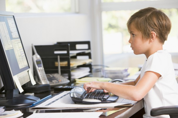 Young boy in home office with computer typing