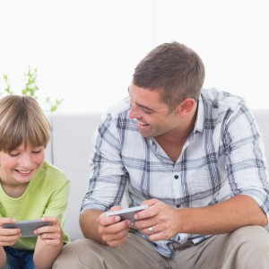 Happy father and son playing games on cell phone at home