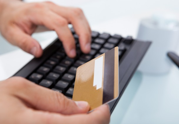 Businessman With Credit Card Shopping Online At Office Desk