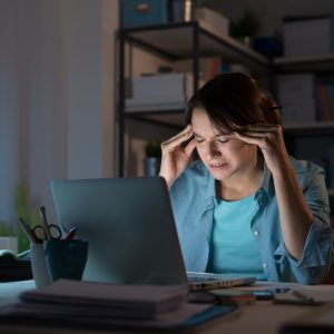 Young woman working with her laptop late at night and having a bad headache, she is touching her temples