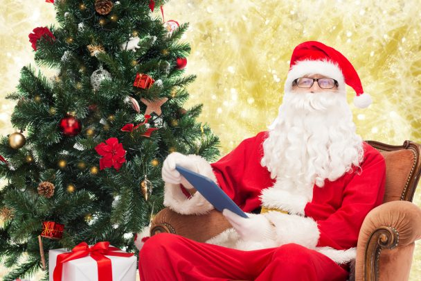 technology, holidays and people concept - man in costume of santa claus with tablet pc computer, gifts and christmas tree sitting in armchair over yellow lights background