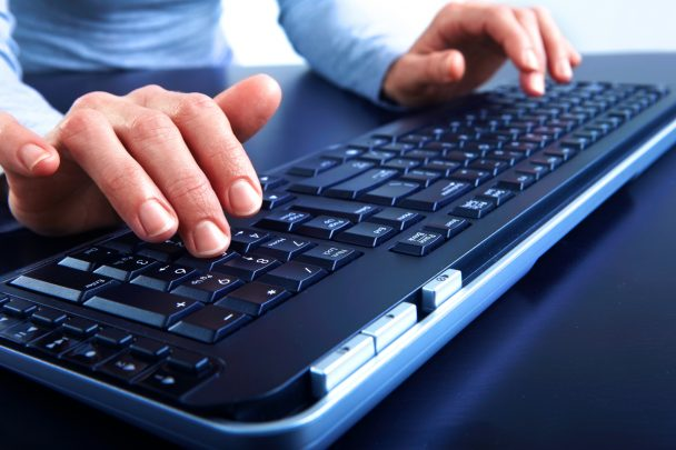 Woman hands typing on the black keyboard
